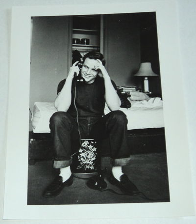 A BEAUTIFUL ORIGINAL PHOTOGRAPH OF A VERY YOUNG MARLON BRANDO, SEATED AT THE TELEPHONE IN FRONT OF HIS UNMADE BED, (Brando, Marlon). Harris, Martin
