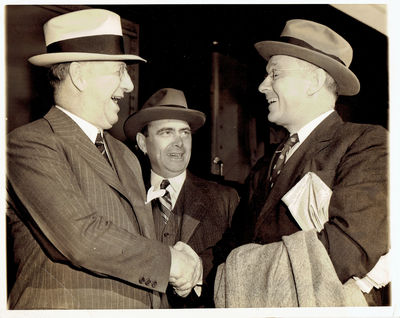 A WONDERFUL VINTAGE 1939 NEWS PHOTOGRAPH DEPICTING FORMER KANSAS GOVERNOR ALF LANDON, WHO HAD PREVIOUSLY RUN FOR THE PRESIDENCY, WITH HIS FORMER RUNNING MATE AS THEY ARRIVE TO ATTEND F.D.R.'S WHITE HOUSE CONFERENCE ON THE NEUTRALITY PROGRAM, (Landon, Alf)