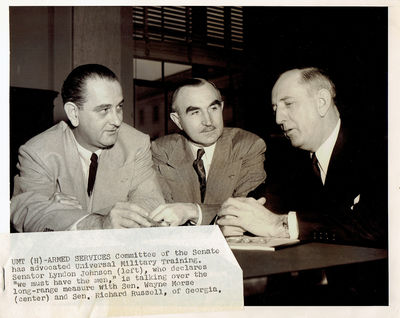 A WONDERFUL VINTAGE NEWS PHOTOGRAPH TAKEN CIRCA 1953-4 DEPICTING THEN-SENATOR LYNDON JOHNSON CHAIRMAN OF THE SENATE ARMED SERVICES COMMITTEE WITH SENATOR WAYNE MORSE AND SENATOR RICHARD RUSSELL OF GEORGIA, (Johnson, Lyndon Baines)